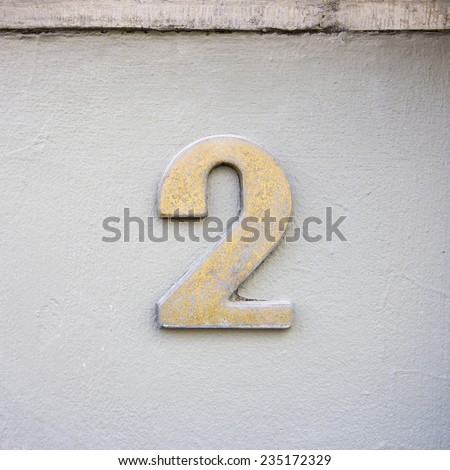 metal house number two on a white stucco wall - stock photo