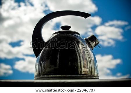 metal kettle against a backdrop of blue sky