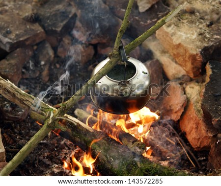 Metal kettle boiling over open fire pit in outback setting - stock photo