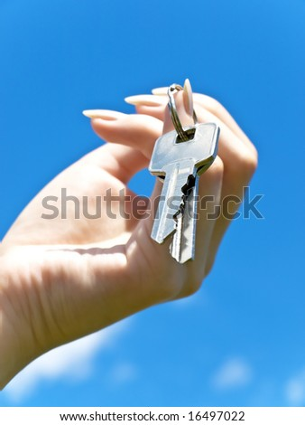 metal key at nail in woman hand against blue sky