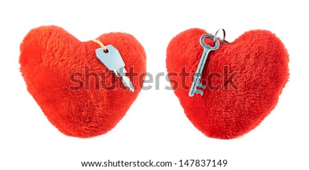Metal key over a red plush heart isolated against white background