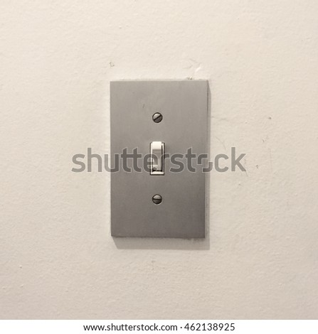 Metal light switch cover with light turned on, white wall