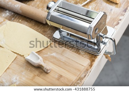 Metal machine to make the dough and fresh pasta for lasagna. Italian cooking - stock photo