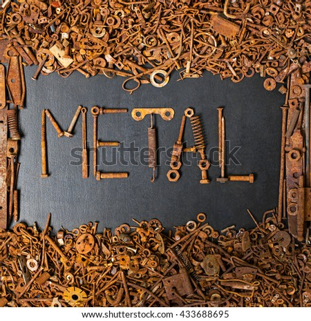 METAL made with rusty screws and bolts on black board with frame consisted of junk metal - stock photo