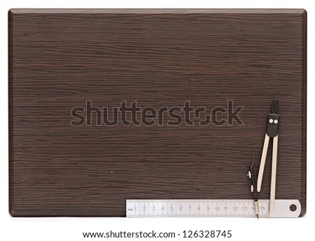 Metal measuring devices on wooden plate including ruler and compass - stock photo