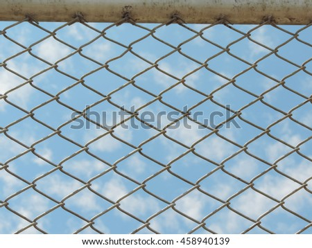 Metal mesh wire fence with noon day light and blur blue background.