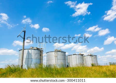 Metal modern silos on the large green field