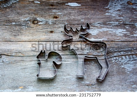 Metal molds for Christmas cookies on rustic wooden texture, top view - stock photo