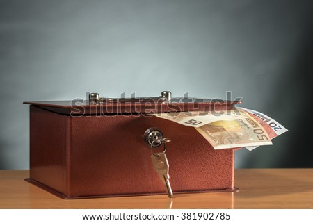 Metal moneybox with several euro banknotes sticking out - stock photo
