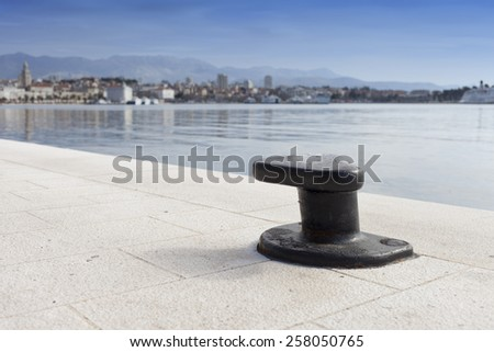 Metal mooring bollard on the dock of concrete harbor pier, against coastal town, selective focus on bollard, space for text - stock photo