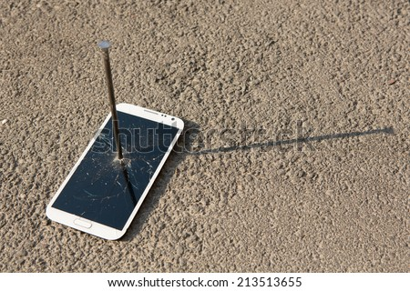 metal nail and smart-phone with a broken screen over the stone surface - stock photo
