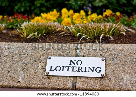 Metal No Loitering Sign on Concrete Wall - stock photo