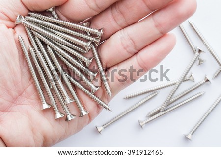 metal nut screw on man hand for adhesive material. - stock photo