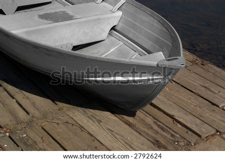 Metal old-fashioned row-boat sitting on the dock waiting for use - stock photo
