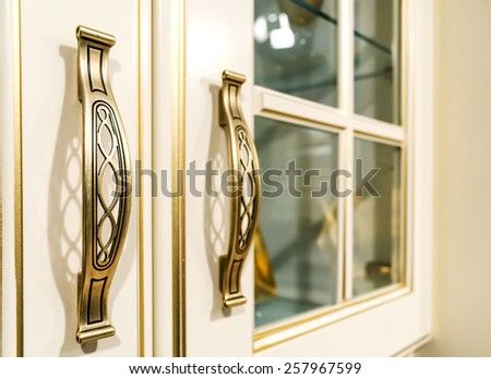 metal ornate handle on a wooden cupboard  - stock photo