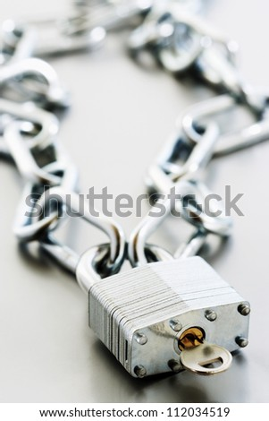 Metal padlock with key and chain - stock photo