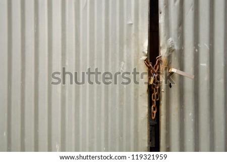 Metal Padlocked Door - Old iron door closed by chain and padlock - stock photo