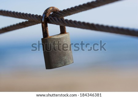 Metal padlocks of love hanging on fence - stock photo