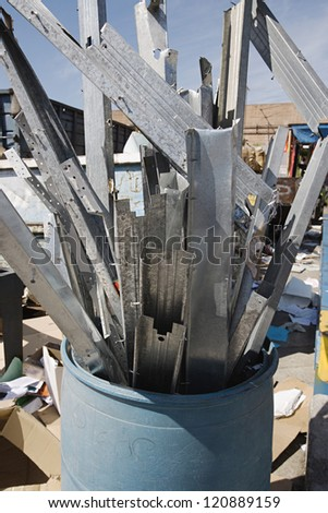 Metal parts in garbage bin at junkyard - stock photo