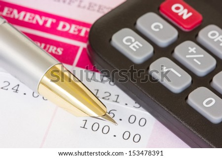 Metal pen, calculator and payslip with monthly wage - stock photo
