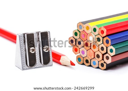 Metal pencil sharpener next to colorful crayons - stock photo
