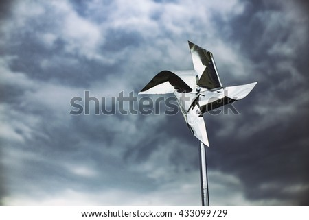 metal pinwheel on a background of the storm sky. silver pinwheel spinning in the wind against a dark sky. copy space for your text - stock photo
