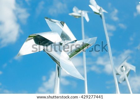 metal pinwheels on background blue sky. silver pinwheel spinning in the wind against cloudy sky - stock photo