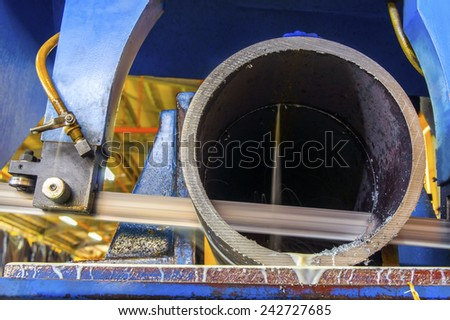 metal pipe cutting with power saw - stock photo