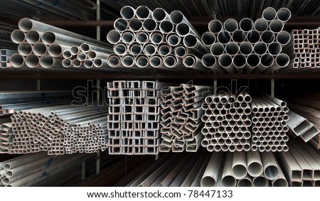 Metal pipe stack on shelf - stock photo