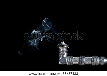 metal pipe used for drug abuse with smoke coming out of it on black background - stock photo