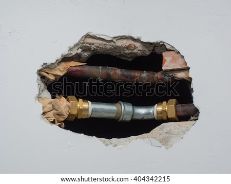 metal  pipes and fittings of domestic water supply system seen through a hole in a white wall - stock photo