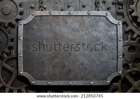 Metal plate hanging on chains over medieval gears and cogs - stock photo