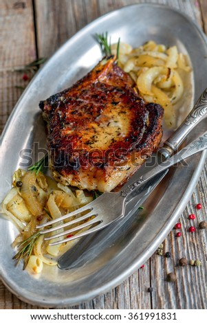 Metal plate  with pork chops, rosemary and roasted onions.