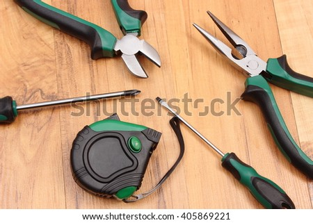 Metal pliers, electrical screwdrivers and tape measure on wooden surface, work tools and accessories for engineering jobs - stock photo