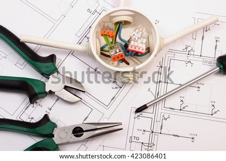 Metal pliers, screwdriver and cable connections in electrical box lying on electrical construction drawing of house, work tool and drawing for engineer jobs - stock photo