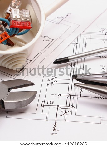 Metal pliers, screwdriver and cable connections in electrical box on electrical construction drawing, work tool and drawing for engineer jobs, concept of building house - stock photo