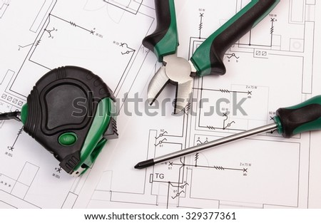Metal pliers, screwdriver and tape measure on electrical construction drawing of house, work tools and drawing for projects engineer jobs, concept of building house - stock photo