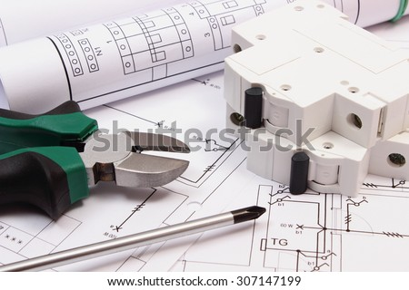 Metal pliers, screwdriver, electric fuse and rolls of diagrams on electrical construction drawing of house, work tool and drawing for engineer jobs, concept of building house - stock photo