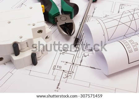 Metal pliers, screwdriver, electric fuse and rolls of diagrams on electrical construction drawing of house, work tool and drawing for projects engineer jobs, concept of building house - stock photo