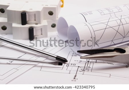Metal pliers, screwdriver, electric fuse and rolls of diagrams on electrical construction drawing, work tool and drawing for projects engineer jobs, concept of building house - stock photo