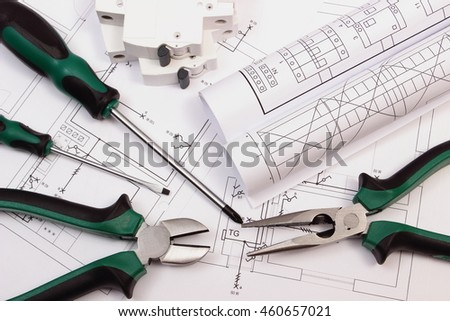 Metal pliers, screwdriver, electric fuse and rolls of diagrams on electrical construction drawing of house, accessories for projects engineer jobs, concept of building house - stock photo