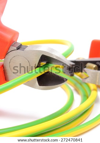 Metal pliers with tangled green-yellow electric cable, pliers cut the cable. Isolated on white background - stock photo