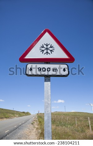 metal pole with traffic signal advice danger snow at 900 metres in rural road next to Madrid Spain Europe - stock photo