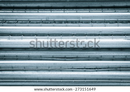 Metal poles stacked as an abtract background image in cold monochrome - stock photo