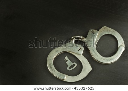 Metal police handcuffs on a dark wooden board. Silver handcuffs. Security concept on wooden background. Closed handcuffs. Equipment police officer. Crime and Punishment. - stock photo