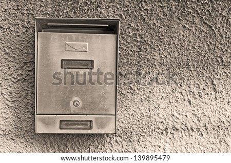 metal post  box on rustic wall in sepia tone - stock photo