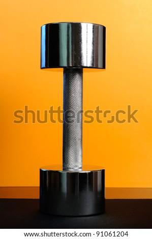 Metal 10-Pound Dumbbell on Yellow Background - stock photo