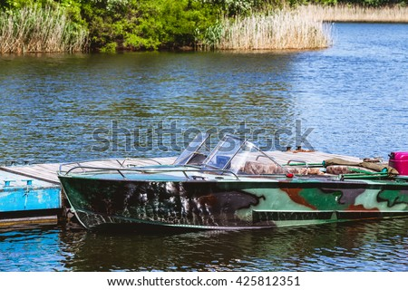 Metal powerboat camouflage painting is at the berth in the beautiful Gulf summer day  - stock photo