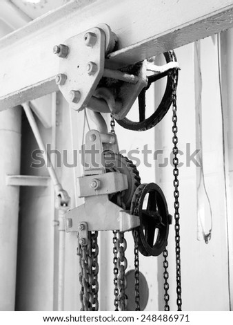 Metal pulley with chains, detailed close-up view in black and white - stock photo
