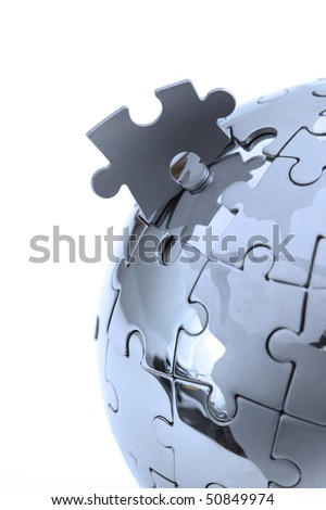 Metal puzzle globe isolated on white background, close-up in blue light - stock photo
